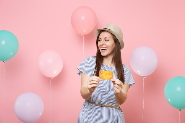 Retrato de mujer joven hermosa alegre en vestido azul de sombrero de paja de verano con tarjeta de crédito mirando a un lado sobre fondo rosa con globos de colores. fiesta de cumpleaños personas emociones sinceras.