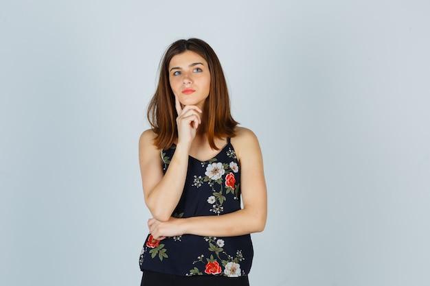 Retrato de mujer joven hermosa apuntando la barbilla en la mano en blusa