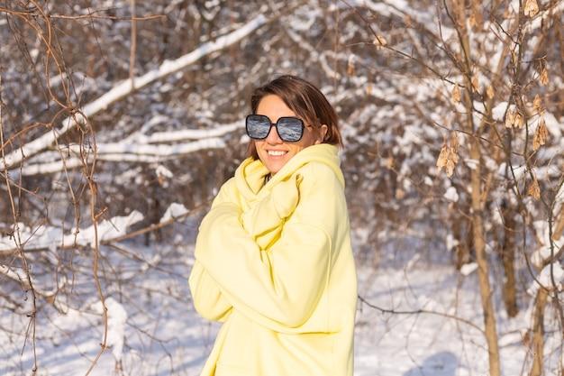 Retrato de una mujer joven y hermosa en un bosque de invierno paisaje nevado en un día soleado, vestida con un gran jersey amarillo, con gafas de sol, disfrutando del sol y la nieve