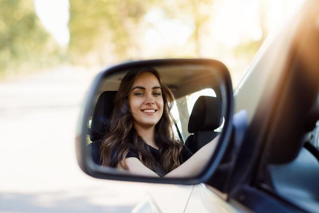 Retrato de mujer joven hermosa en el coche nuevo mirando tirar el espejo retrovisor