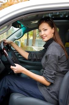 Retrato de mujer joven hermosa en el coche nuevo