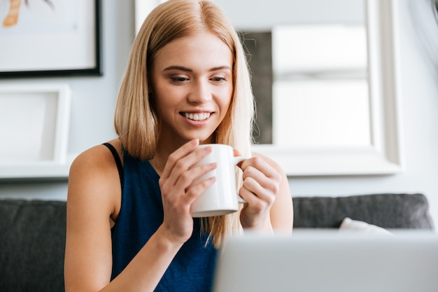 Retrato de mujer joven hermosa feliz bebiendo café en casa