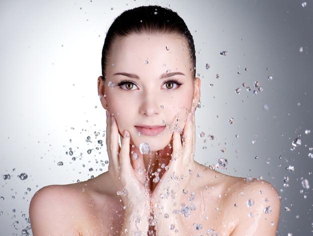 Retrato de mujer joven hermosa con gotas de agua alrededor de su rostro