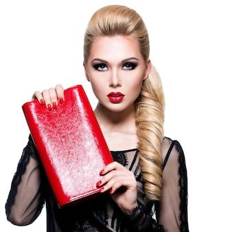 Retrato de mujer joven hermosa con uñas y labios rojos brillantes. concepto - maquillaje de moda glamour