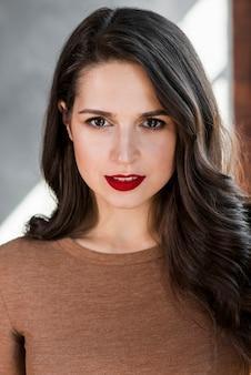 Retrato de una mujer joven hermosa en el lápiz labial rojo que mira la cámara
