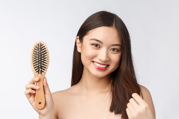 El retrato de una mujer joven hermosa peina el pelo maravilloso aislado en el fondo blanco, belleza asiática