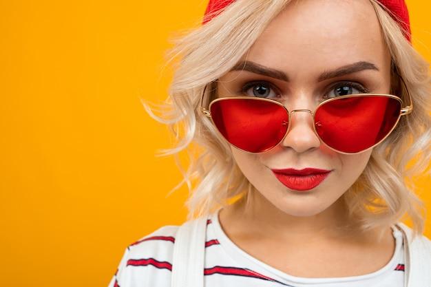 Retrato de mujer joven hermosa con el pelo rizado rubio corto y maquillaje brillante en overoles blancos. gafas de sol rojas y sonrisas de sombrero rojo aisladas en naranja