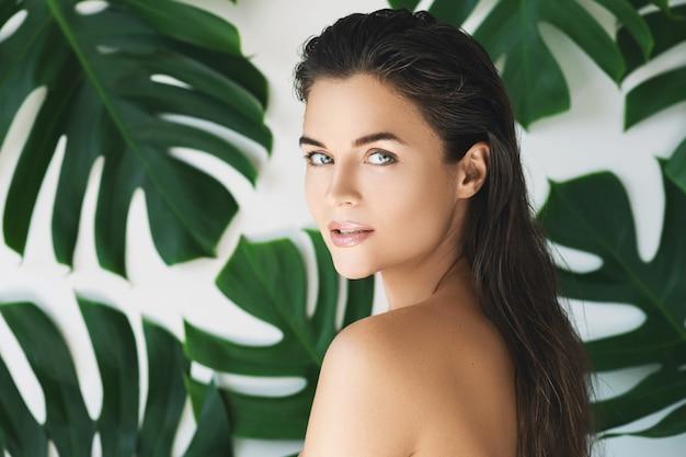 Retrato de mujer joven y hermosa con piel suave perfecta en hojas tropicales