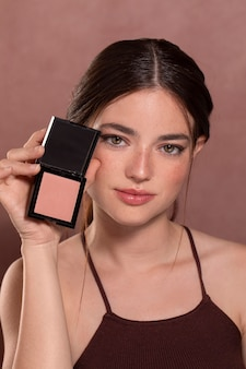 Retrato de mujer joven hermosa con un producto de maquillaje