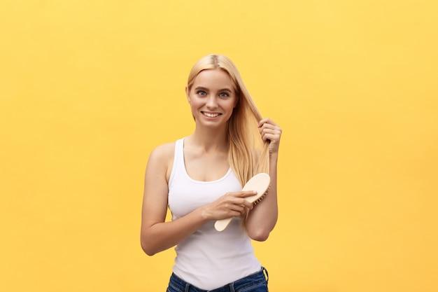 Retrato de la mujer joven hermosa que se peina el pelo, mirando a la cámara y sonriendo.