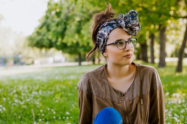Retrato de mujer joven hermosa que se sienta en la hierba verde