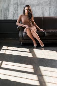 Retrato de una mujer joven hermosa que se sienta en el sofá que mira la cámara