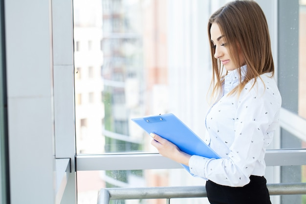 Retrato de mujer joven hermosa que trabaja en la oficina.