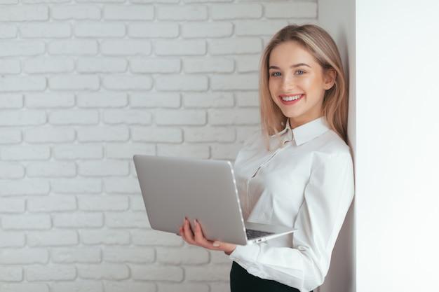 Retrato de la mujer joven hermosa que trabaja en la oficina.