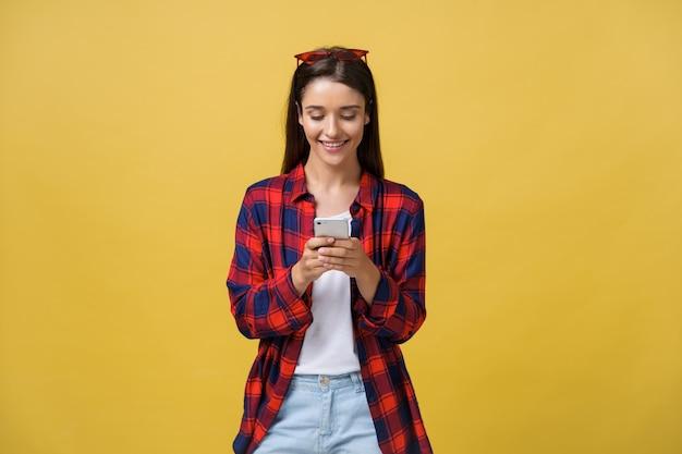 Retrato de la mujer joven hermosa que usa el teléfono móvil aislado en fondo amarillo