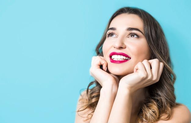 Retrato de una mujer joven hermosa sonriente, dientes blancos sanos. chica cara con lápiz labial rojo.
