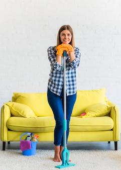 Retrato de mujer joven hermosa sonriente con equipos de limpieza