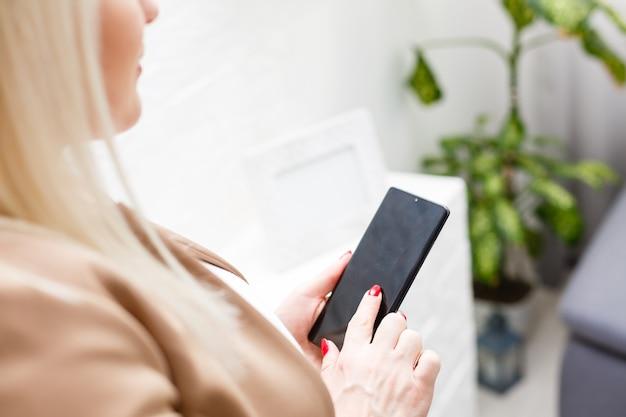 Retrato de mujer joven hermosa con su teléfono móvil en casa.