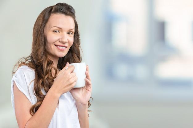 Retrato de mujer joven y hermosa tomando café
