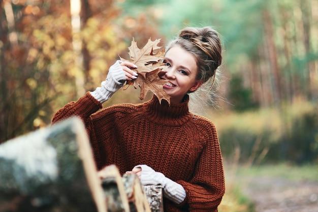 Retrato de mujer joven con hojas otoñales en el bosque