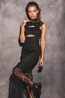 Retrato de mujer joven inconformista hermoso vestido de verano negro de moda. mujer despreocupada sexy posando junto a la pared. modelo morena con maquillaje y peinado