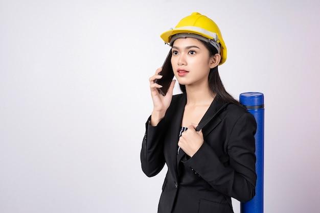Retrato de mujer joven ingeniero con móvil con casco