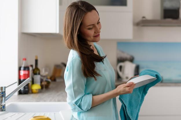 Retrato de una mujer joven en el interior de la cocina limpie con una toalla seca platos limpios, limpiando la casa
