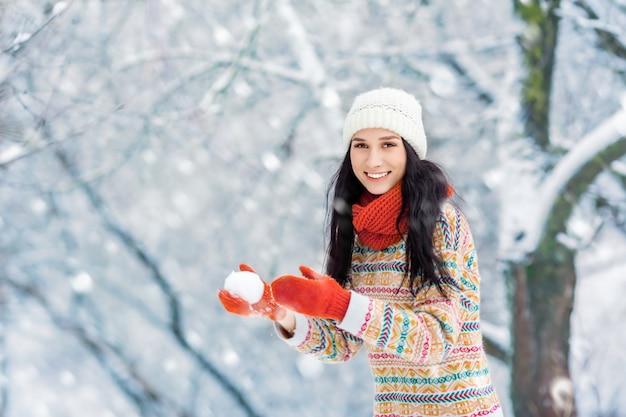 Retrato de mujer joven de invierno. belleza alegre modelo chica riendo y divirtiéndose en el parque de invierno