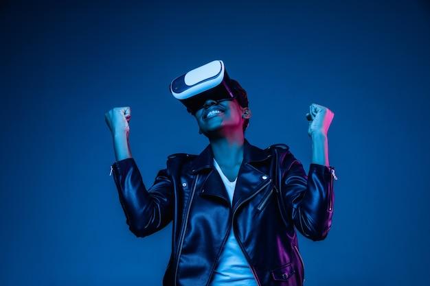 Retrato de mujer joven jugando en gafas vr en luz de neón en azul
