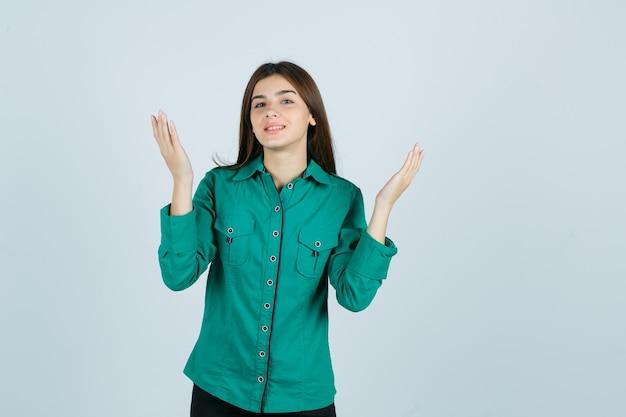 Retrato de mujer joven levantando las manos mientras sonríe en camisa verde y mira esperanzada vista frontal