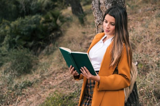 Retrato de una mujer joven leyendo el libro bajo el árbol