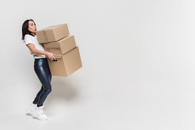 Retrato de mujer joven llevando cajas de cartón