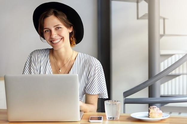 Retrato, de, mujer joven, llevando, sombrero grande, y, utilizar la computadora portátil