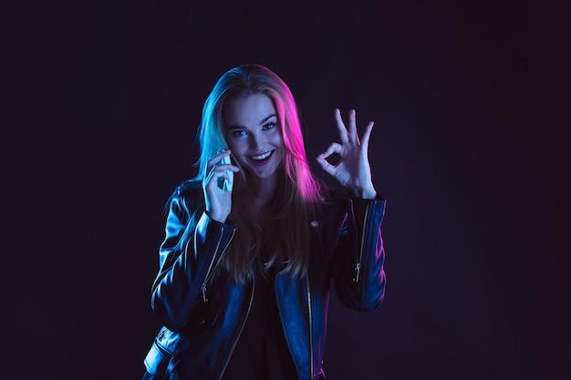 Retrato de mujer joven en luz de neón sobre fondo oscuro.