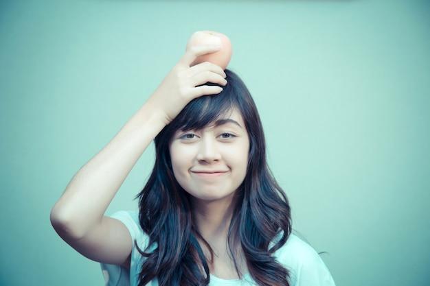 Retrato de mujer joven con manzana en la cabeza. concepto de cuidado saludable