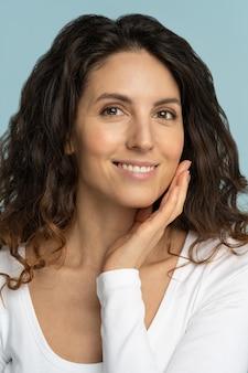 Retrato de mujer joven con maquillaje natural, cabello rizado, tocando la piel pura bien cuidada en la cara