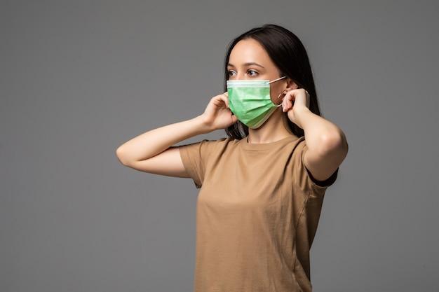Retrato de una mujer joven en una máscara médica aislada en gris