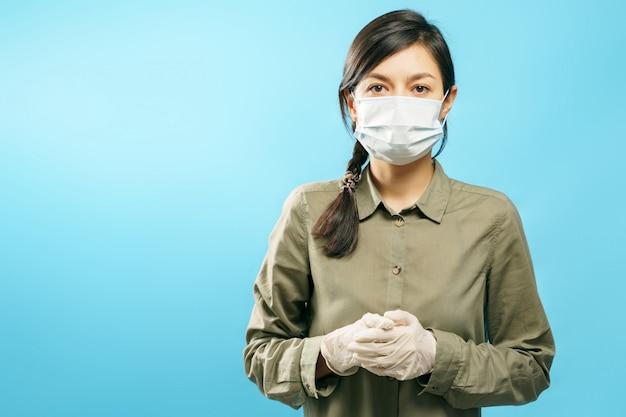Retrato de una mujer joven en una máscara médica protectora y guantes sobre un fondo azul.