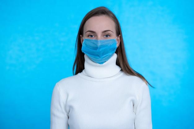 Retrato de mujer joven con máscara médica en superficie azul proteja su salud concepto de coronavirus