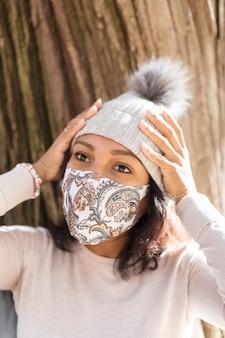 Retrato de mujer joven con una mascarilla. ella se lleva las manos a la cabeza.