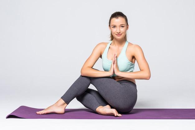 Retrato de mujer joven meditando en pose de loto aislado