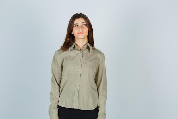 Retrato de mujer joven mirando hacia arriba mientras curva los labios en camisa