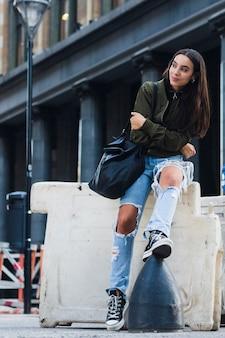 Retrato de una mujer joven de moda con el bolso que se sienta en la calle
