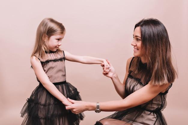 Retrato de mujer joven de moda con niña linda con vestidos negros similares posando en la pared beige con verdaderas emociones. aspecto familiar elegante de madre e hija