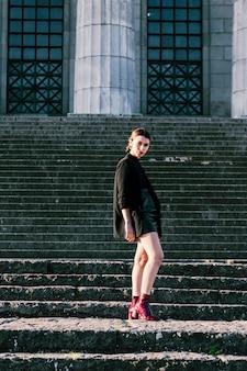 Retrato de una mujer joven de moda de pie en la escalera