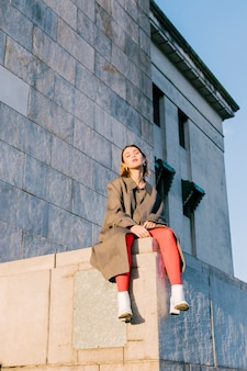 Retrato de una mujer joven de moda que se sienta sobre la pared