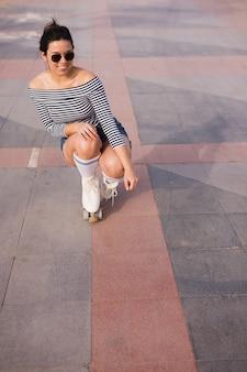 Retrato de una mujer joven de moda sonriente que se agacha en el piso