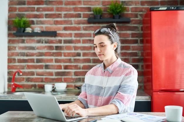 Retrato de mujer joven moderna usando la computadora portátil en casa haciendo blogs o trabajo independiente