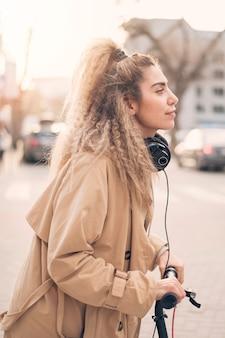 Retrato de mujer joven montando scooter eléctrico