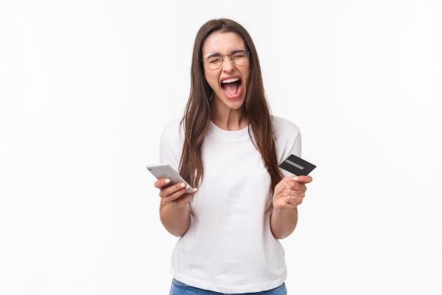Retrato de mujer joven morena molesta y enojada incómoda en camiseta gritando cabreado como cuenta corriente bancaria, no tiene dinero en la tarjeta de crédito, o venció